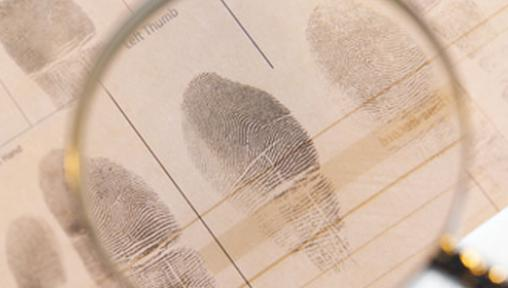 looking at finger prints through magnifying glass