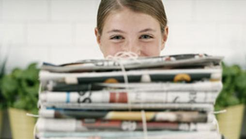 girl behind stack of newspapers