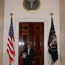 Braeden holding his football helmet, standing between two flags at White house door.