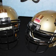 Two golden football helmets on a table